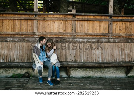 Young couple in love wrapped in plaid sitting and having fun - stock photo