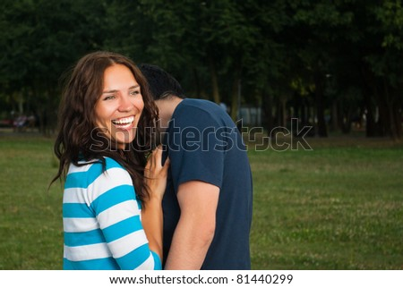 Young couple in park laughing - stock photo