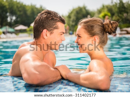 Young couple in pool. They are looking at each other and smiling. - stock photo