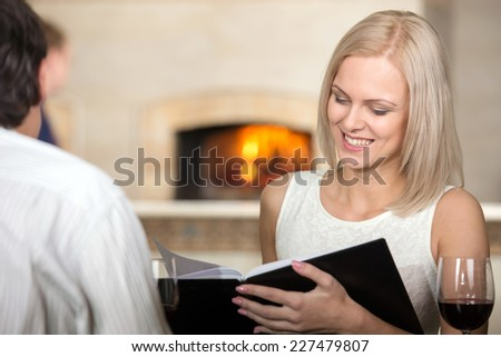Young couple in restaurant cheering with red wine. The woman are looking at the menu-card and smiling. - stock photo