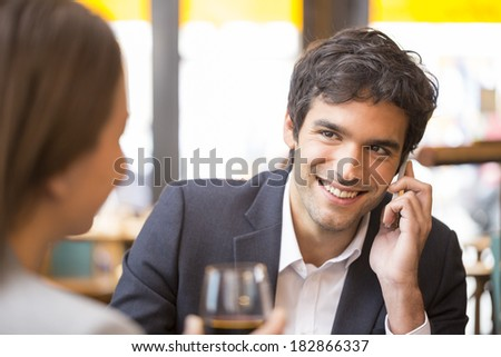 Young couple in restaurant, man is on the phone - stock photo
