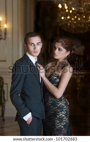 Young couple in royal interior - stock photo