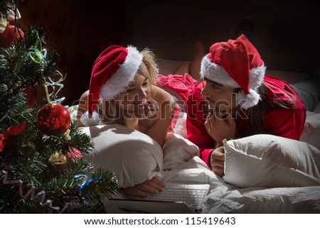Young couple in Santa's hats  in white bed - stock photo