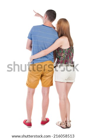young couple in shorts and t-shirt pointing. Back view.  Rear view people collection.  backside view of person.  Isolated over white background. - stock photo