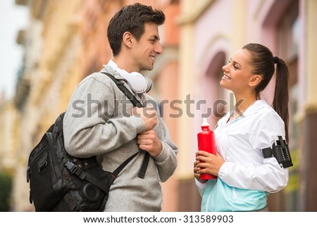 Young couple in sportswear with bottles of water. Outdoor. - stock photo