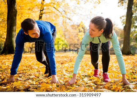 Young couple in steady position prepared for running in autumn nature - stock photo
