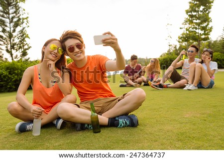 Young couple in sunglasses taking selfie at the party - stock photo