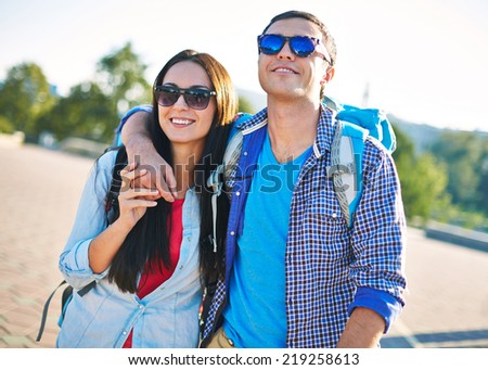 Young couple in sunglasses traveling in a city - stock photo