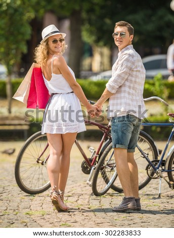 Young couple in sunglasses with bicycles holding hands on the city square. Woman holding shopping bags. Rear view. - stock photo