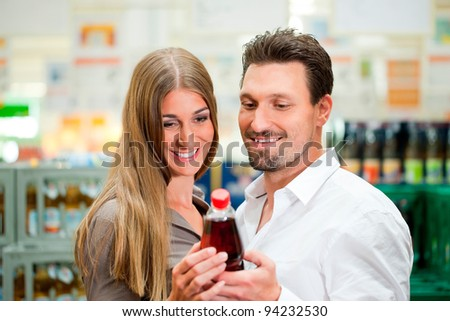 Young couple in supermarket buying beverages together - stock photo