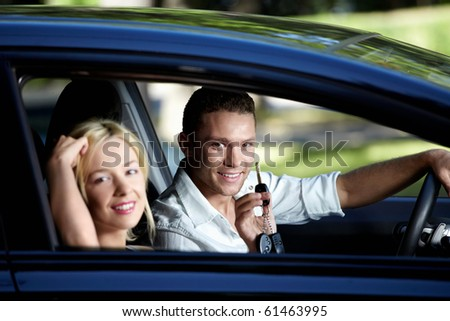 Young couple in the car with the keys - stock photo