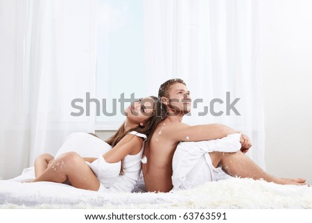 Young couple in the feathers on the bed - stock photo