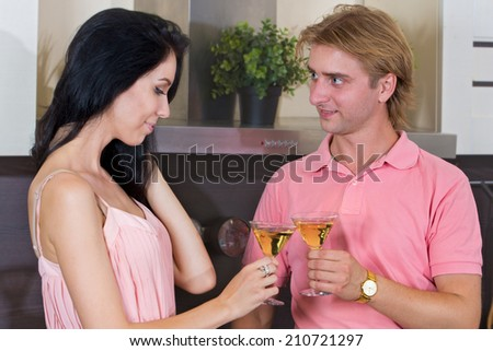 Young couple in the kitchen drinking wine and happy - stock photo