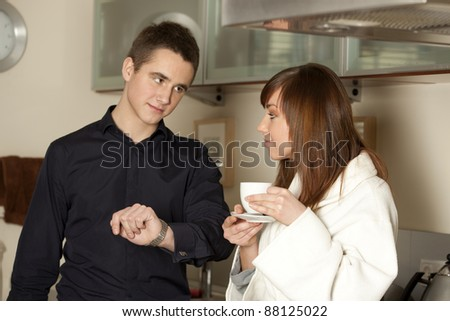 Young couple in the morning drinking coffee in the kitchen - stock photo
