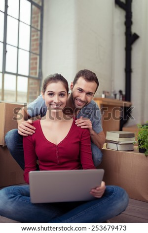 Young couple in their new home sitting on the floor with a laptop looking at the camera with beaming smiles of pleasure with cardboard cartons visible behind - stock photo