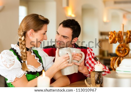 Young couple in traditional Bavarian Tracht in restaurant or pub with pretzel and beer - stock photo