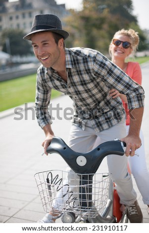 young couple in vacation having fun on a rental bike in the city, in summer - stock photo