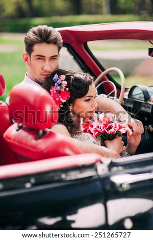 Young couple in vintage cars - stock photo