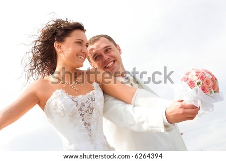 young couple in wedding wear with bouquet of roses. - stock photo