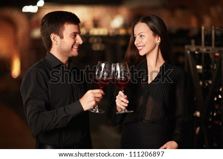 Young couple in wine cellar - stock photo