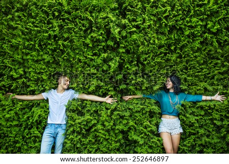 Young couple is closing his eyes back on the bright green foliage. Arms spread wide, hands reaching out to each other. Top view. - stock photo