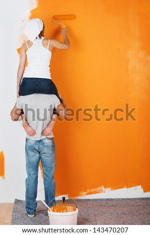 Young couple is having fun painting a wall - stock photo