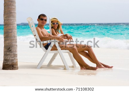Young couple is relaxing on a tropical beach under a palm - stock photo