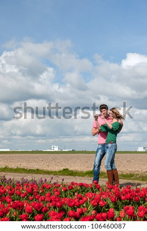 Young couple is taking pictures in Holland from flower fields - stock photo