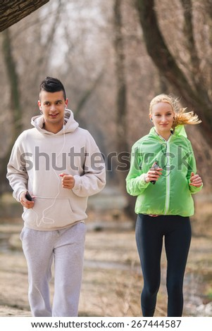 Young couple jogging and listening to music - stock photo
