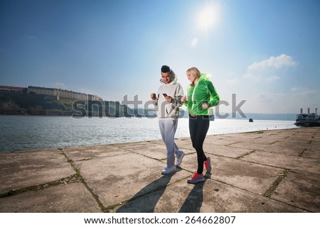 Young couple jogging by the river. Young man holding a mobile phone. - stock photo