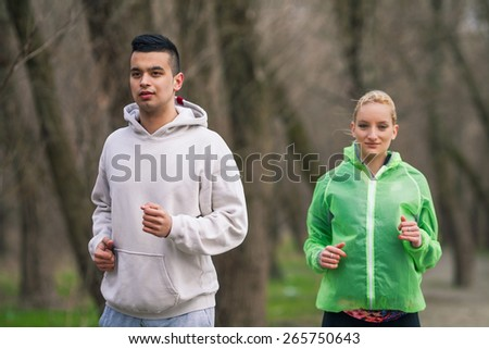 Young couple jogging in nature - stock photo