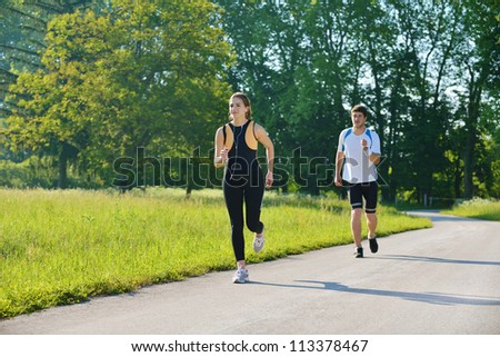 Young couple jogging in park at morning. Health and fitness concept - stock photo