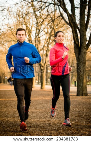 Young couple jogging together in tree alley - late autumn - stock photo