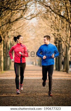 Young couple jogging together in tree alley - looking on each other - stock photo