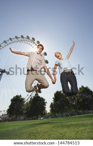 Young couple jumping in air in front of London Eye at a park - stock photo