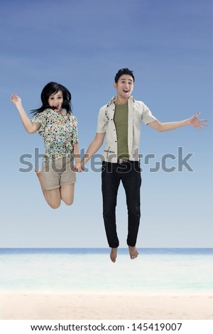 Young couple jumping on the white sand beach - stock photo