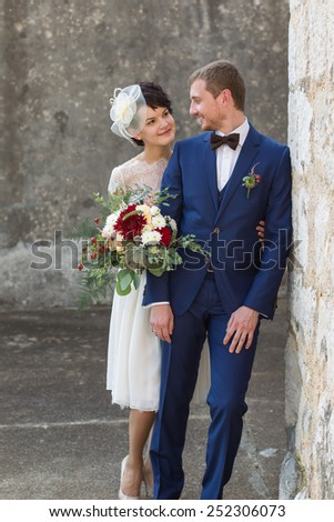young couple just married people standing near a wall smiling and looking at each other - stock photo