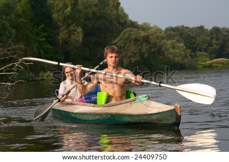 young couple kayaking on the river - stock photo