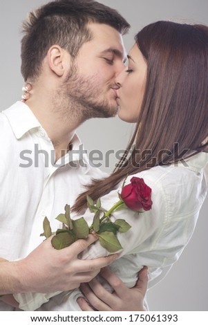 Young couple kissing and holding one red rose - stock photo