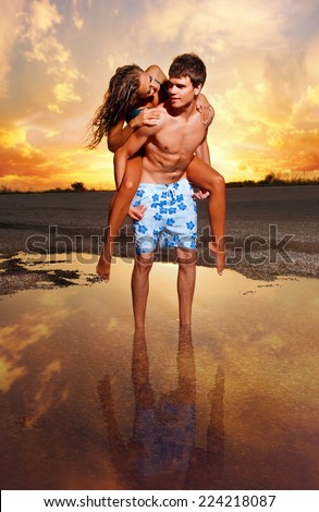 young couple kissing at the beach with the sun setting behind them - stock photo