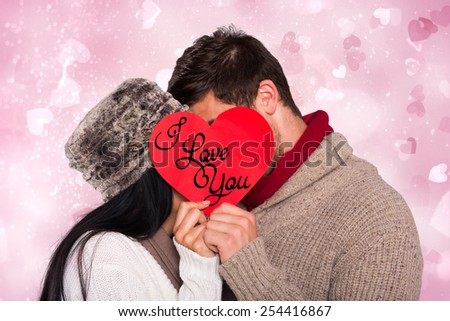 Young couple kissing behind red heart against valentines heart design - stock photo