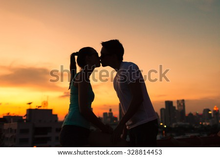 Young couple kissing in a beautiful city setting. - stock photo