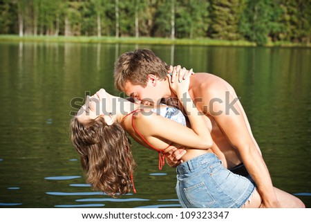 Young couple kissing in a montain lake - stock photo