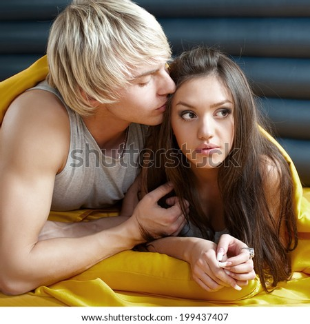 young couple kissing in bed - stock photo