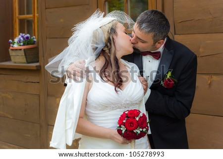 Young couple kissing in front of an vintage house - stock photo