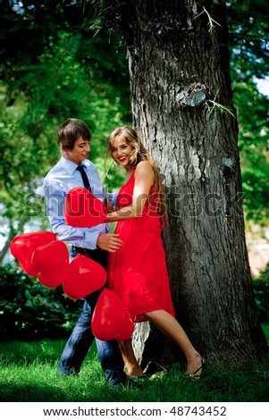 Young couple kissing in green park near tree - stock photo