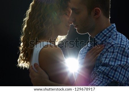 Young couple kissing in the dark - stock photo