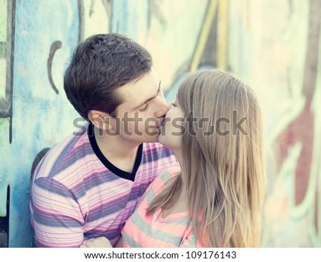 Young couple kissing near graffiti background. - stock photo