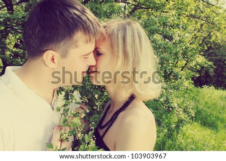 Young couple kissing near the blooming hawthorn - stock photo