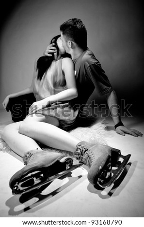 Young couple kissing on floor.Woman wearing ice skating boots - stock photo